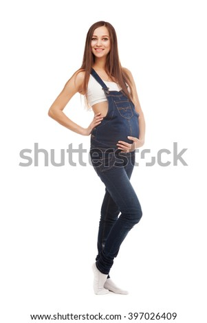 Full length portrait of a beautiful pregnant woman in jean overall against white background - stock photo