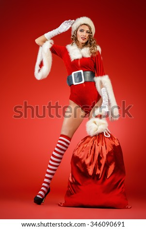 Full length portrait of a beautiful sexy Christmas girl holding big sack with gifts. Red background. - stock photo