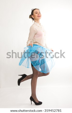 Full length portrait of a beautiful sexy slim model in blue skirt and white blouse transparent, in stockings and garters