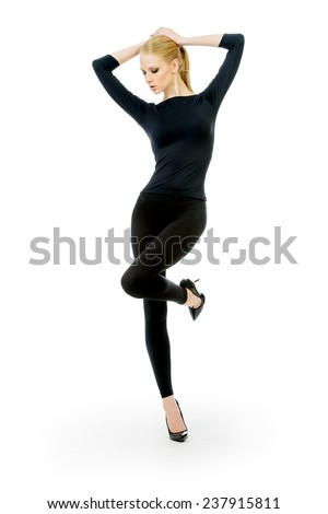 Full length portrait of a beautiful slender female model in black fitting clothing posing over white background. Beauty, fashion. Body care. Isolated over white. - stock photo