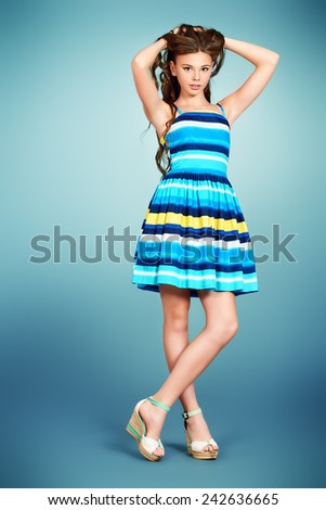 Full length portrait of a beautiful smiling girl teenager with long curly hair posing in bright summer dress. Studio shot. - stock photo