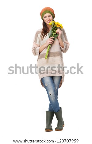 Full length portrait of a beautiful smiling young woman wearing a hat and boots. She is holding yellow flowers and isolated on white background - stock photo