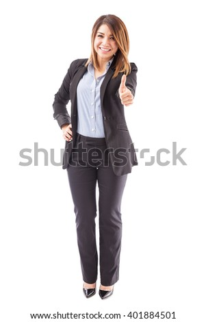 Full length portrait of a beautiful woman in a suit giving a thumb up and inviting people to like her business page - stock photo