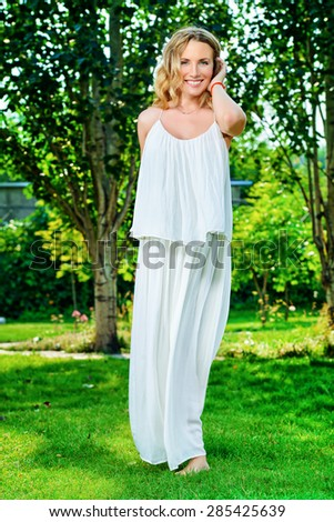 Full length portrait of a beautiful woman in light white dress standing in the summer park. Beauty, fashion. - stock photo