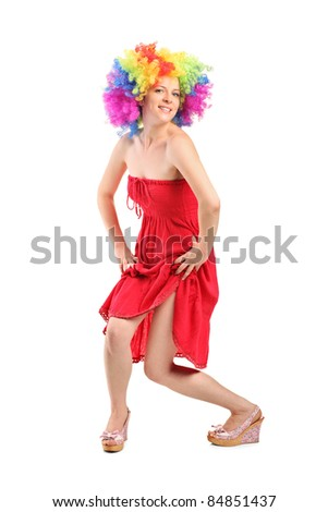 Full length portrait of a beautiful woman in rainbow clown wig with freckles posing isolated on white background - stock photo