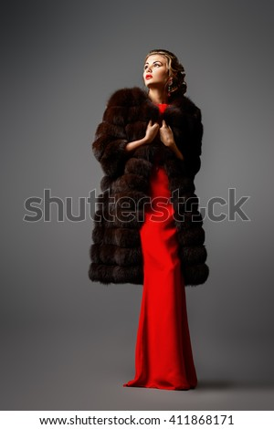 Full length portrait of a beautiful woman in red dress and luxurious fur coat. Luxury, rich lifestyle. Fashion shot.  - stock photo