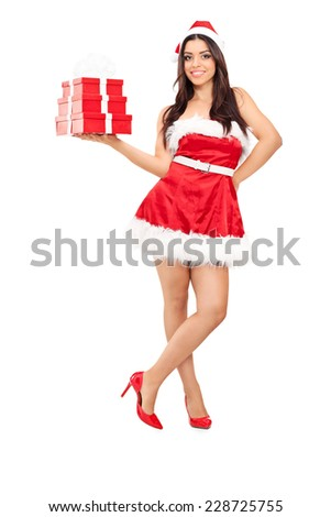 Full length portrait of a beautiful woman in Santa costume holding presents isolated on white background - stock photo