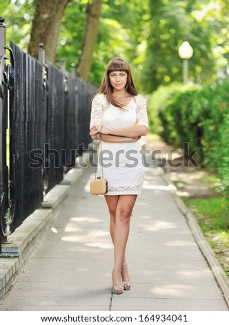 Full length portrait of a beautiful woman in summer park
