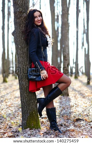 Full length portrait of a beautiful woman leaning on a tree trunk - stock photo