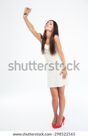 Full length portrait of a beautiful woman making selfie photo on smartphone isolated on a white background - stock photo