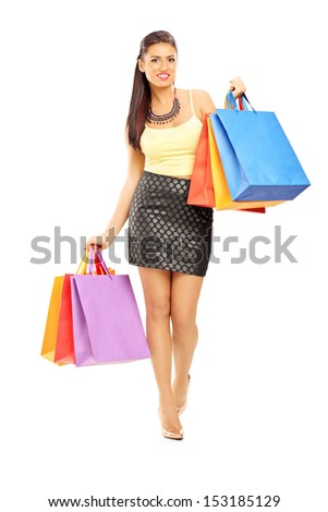 Full length portrait of a beautiful woman walking with shopping bags, isolated on white background - stock photo