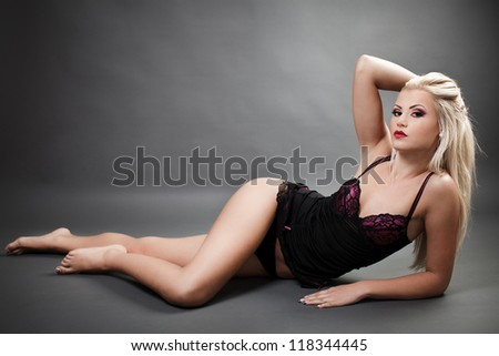 Full length portrait of a beautiful woman wearing lingerie while laying on the floor - stock photo