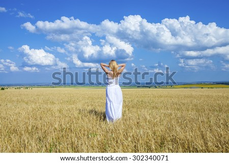 Full length portrait of a beautiful young woman in a white dress walking through the wheat field - stock photo