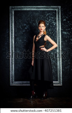 Full length portrait of a beautiful young woman in long black dress and earrings and necklace with gems. Jewellery. Beauty, fashion. Studio shot.  - stock photo