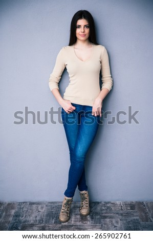 Full length portrait of a beautiful young woman leaning on the gray wall. Looking at camera.
