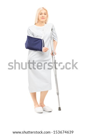 Full length portrait of a blond female patient in hospital gown with broken arm and crutch isolated on white background