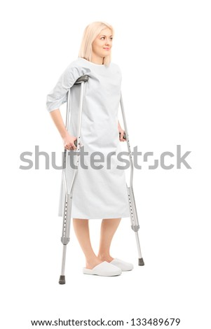 Full length portrait of a blond female patient in hospital gown with crutches isolated on white background