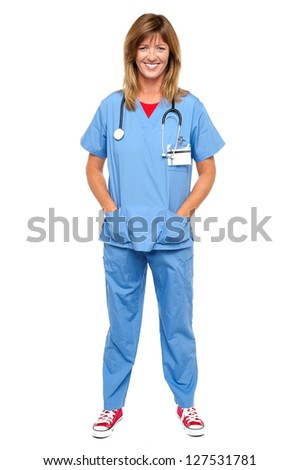 Full length portrait of a blonde doctor in uniform posing with hands in pocket. - stock photo