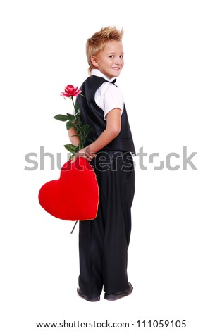Full length portrait of a boy hiding heart pillow and rose behind his back