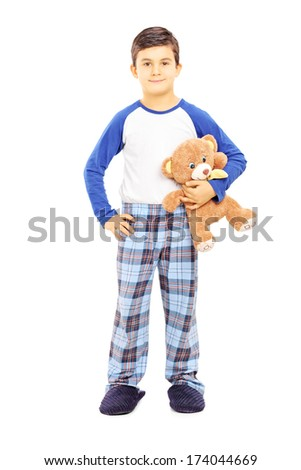 Full length portrait of a boy in pajamas holding teddy bear isolated on white background - stock photo