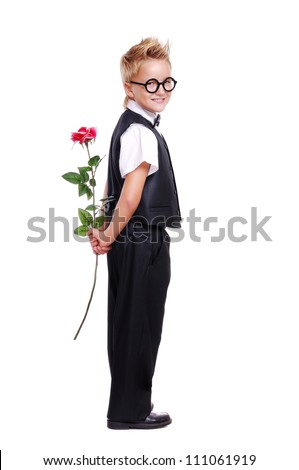 Full length portrait of a boy in suit and bow tie holding a rose - stock photo