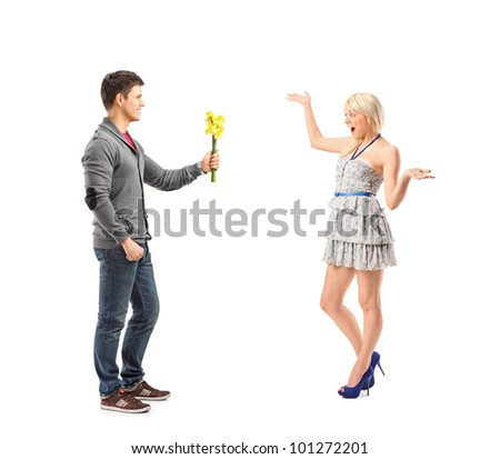 Full length portrait of a boyfriend giving flowers to his excited girlfriend isolated on white background