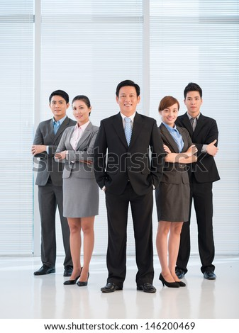 Full-length portrait of a business team looking confidently at camera - stock photo