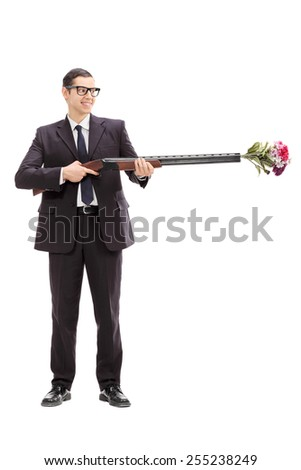 Full length portrait of a businessman holding a rifle loaded with a bouquet of flowers isolated on white background