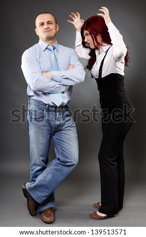 Full length portrait of a businessman ignoring angry businesswoman - stock photo