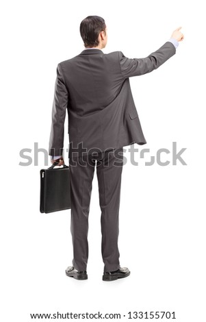 Full length portrait of a businessman pointing in a direction, shot from behind, isolated on white background - stock photo