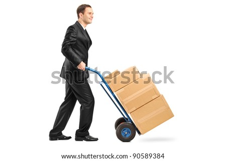 Full length portrait of a businessman pushing a hand truck full with cardboard boxes isolated on white background - stock photo