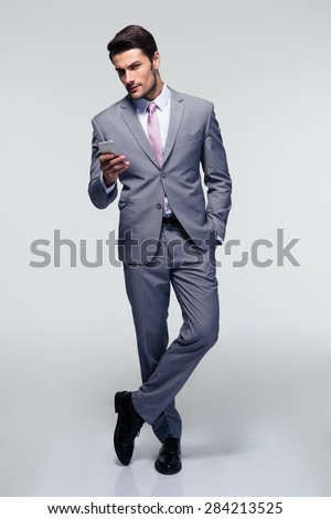 Full length portrait of a businessman standing with smartphone over gray background and looking at camera - stock photo