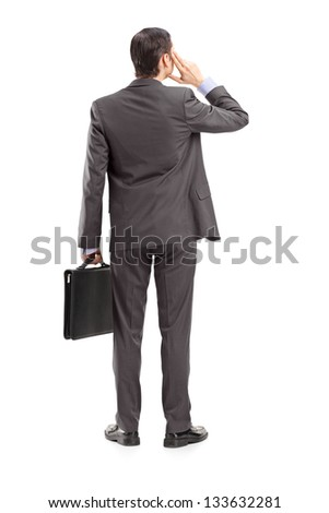 Full length portrait of a businessman thinking, shot from behind, isolated against white background - stock photo