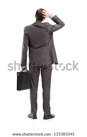 Full length portrait of a businessman with briefcase, holding his head, shot from behind, isolated on white background - stock photo