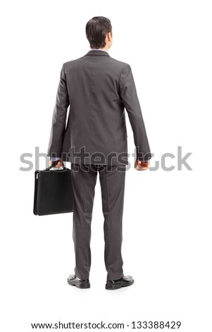 Full length portrait of a businessman with briefcase shot from behind, isolated against white background - stock photo