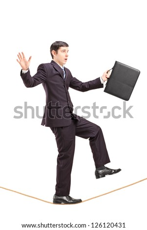 Full length portrait of a businessman with briefcase walking on a rope isolated on white background - stock photo