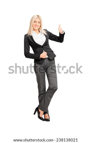 Full length portrait of a businesswoman giving a thumb up and leaning against a wall isolated on white background - stock photo