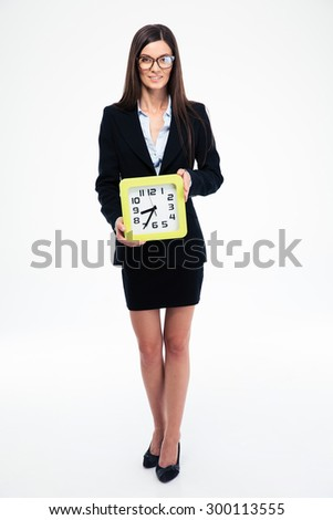 Full length portrait of a businesswoman holding clock isolated on a white background. Looking at camera - stock photo
