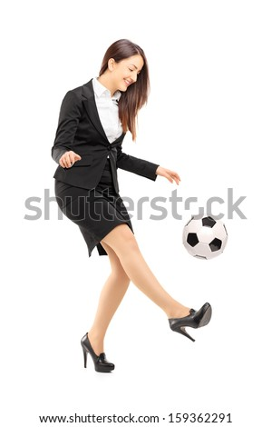 Full length portrait of a businesswoman in high heels kicking a soccer ball isolated on white background - stock photo