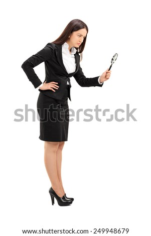 Full length portrait of a businesswoman looking through a magnifying glass isolated on white background - stock photo