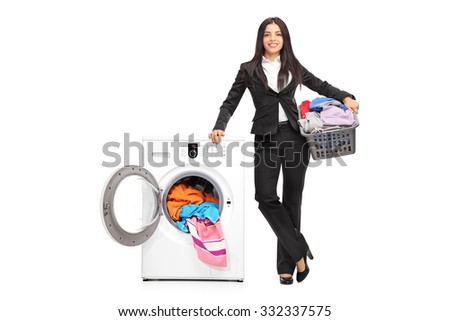 Full length portrait of a businesswoman standing by a washing machine and holding a laundry basket full of clothes isolated on white background - stock photo