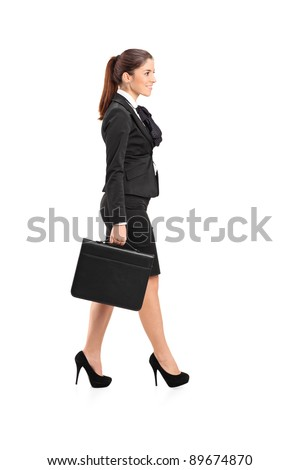 Full length portrait of a businesswoman walking with a briefcase in her hand isolated against white background - stock photo