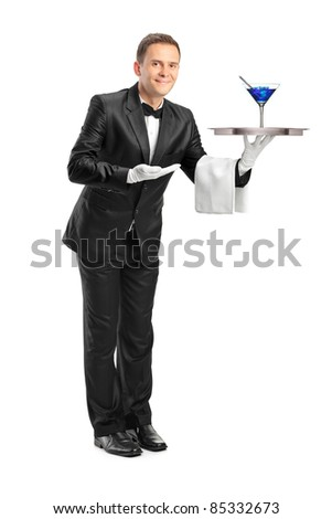 Full length portrait of a butler with bow tie carrying a tray with a cocktail on it isolated against white background