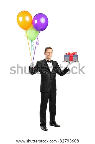 Full length portrait of a butler with bow tie carrying a tray with a gift on it and balloons isolated on white background - stock photo