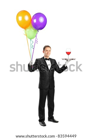 Full length portrait of a butler with bow tie carrying a tray with a wine glass on it and balloons isolated on white background