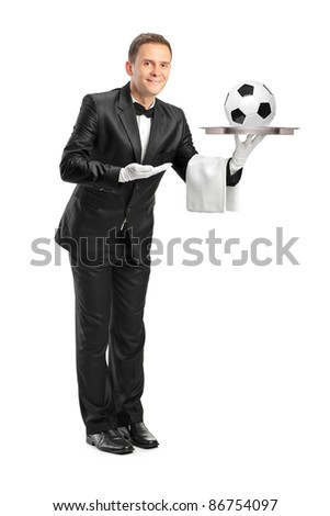 Full length portrait of a butler with bow tie holding a tray with a football on it isolated against white background - stock photo