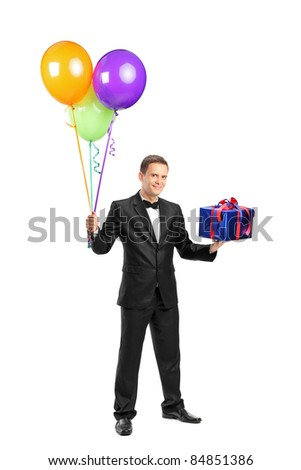Full length portrait of a butler with bow tie holding balloons and a gift isolated against white background - stock photo