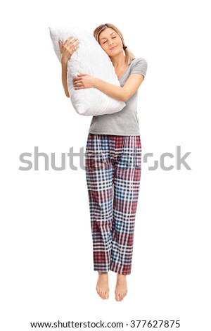 Full length portrait of a calm woman hugging a pillow and sleeping shot in mid-air isolated on white background - stock photo