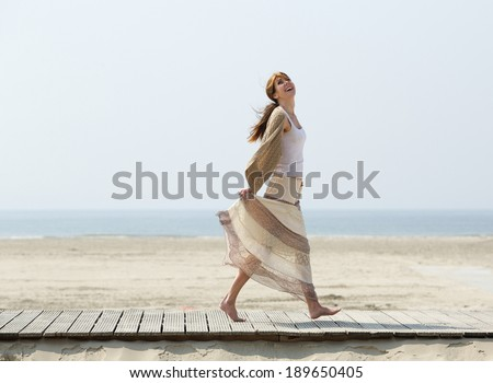 Full length portrait of a carefree middle aged woman walking barefoot at the beach - stock photo