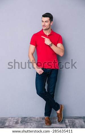 Full length portrait of a casual man pointing away and leaning on the gray wall - stock photo